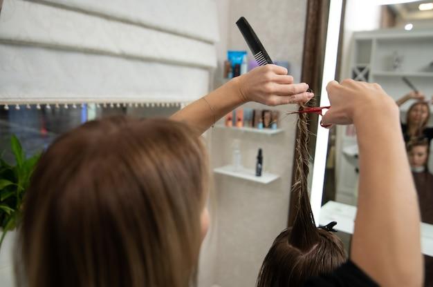 美容院でハサミで金髪の長い髪をトリミングする美容師のトリミングされたビュー