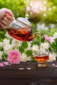Обрезанный вид руки, наливающей чай в элегантную чашку среди цветущих роз и кустов жасмина