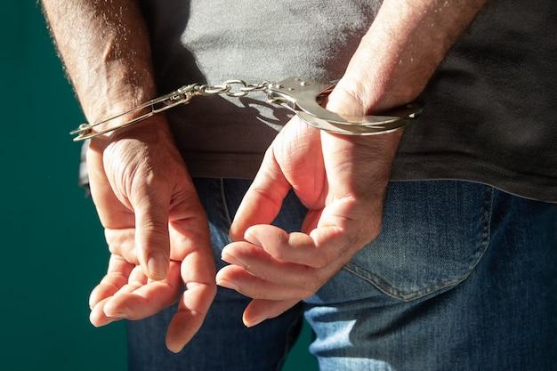 緑に孤立して立っているデニムジーンズの手錠をかけられた男のトリミングされたビュー