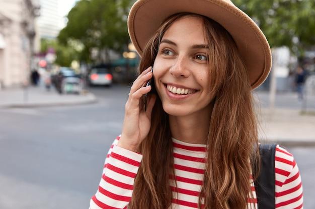 優しい笑顔で幸せなコーカイザン女性のトリミングされたビュー、携帯電話で話し、脇を見る