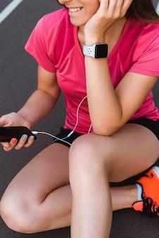 Обрезанное представление о счастливой женщине в smartwatch держит смартфон с пустым экраном на беговой дорожки