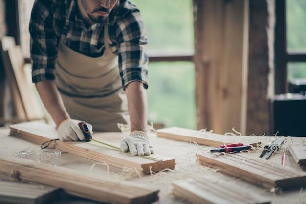 Обрезанный вид его симпатичного, привлекательного, сосредоточенного, опытного профессионального парня, эксперта, измеряющего доску, запускающего проект дома в современном индустриальном стиле лофт