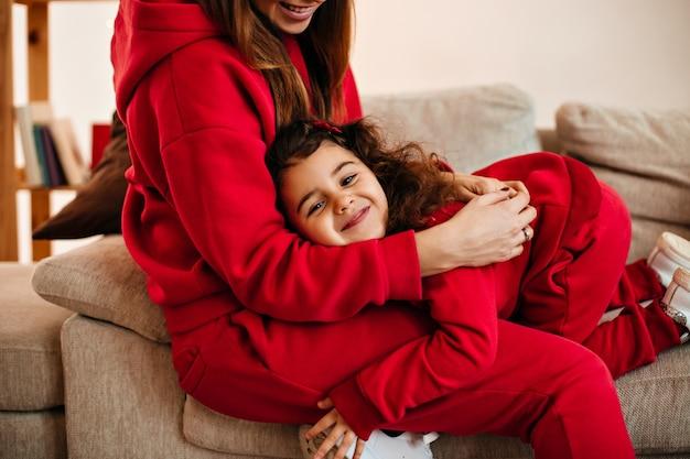 집에서 딸을 껴 안은 웃는 엄마의 자른보기. 웃는 아이가 어머니와 함께 재미의 실내 샷.