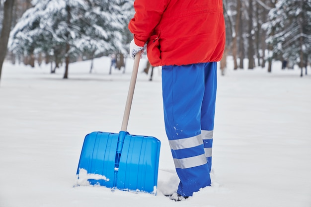 Обрезанный вид мужской уборщик в процессе работы в зимний период