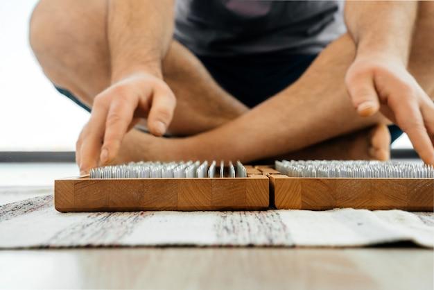 Обрезанный вид человека, занимающегося йогой, медитации и сидящего на полу возле доски садху