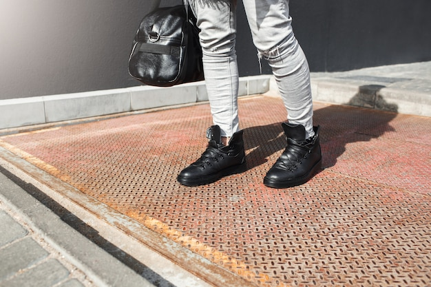 ファッションレザーブーツの男の足のトリミングビュー