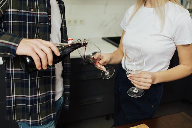 自宅のキッチンで女性にグラスでワインを注ぐ男性のトリミングされたビュー。 Premium写真