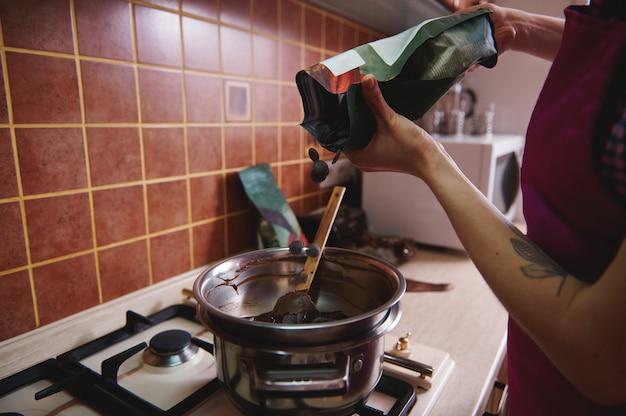 녹은 초콜릿 덩어리를 가열하고 요리하기 위해 초콜릿 정제를 수조에 던지는 생과자 요리사 또는 초콜릿 메이커의 자른보기. 확대