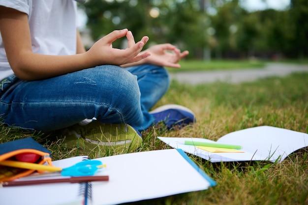 도시 공원의 푸른 잔디에 연꽃 위치에 앉아서 명상하는 학교 소년의 자른 보기. 잔디에 누워 통합 문서 학 용품입니다. 집중, 레크리에이션, 마음챙김 개념
