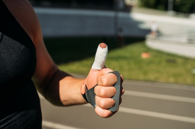 親指を上に表示しているセクシーなボディービルダーのトリミングされたビュー、クローズビュー
