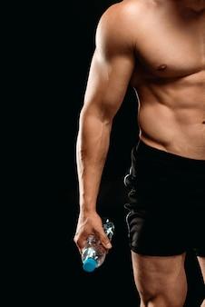 黒に分離された新鮮な水のボトルを保持している筋肉の胴とセクシーなボディービルダーのトリミングビュー