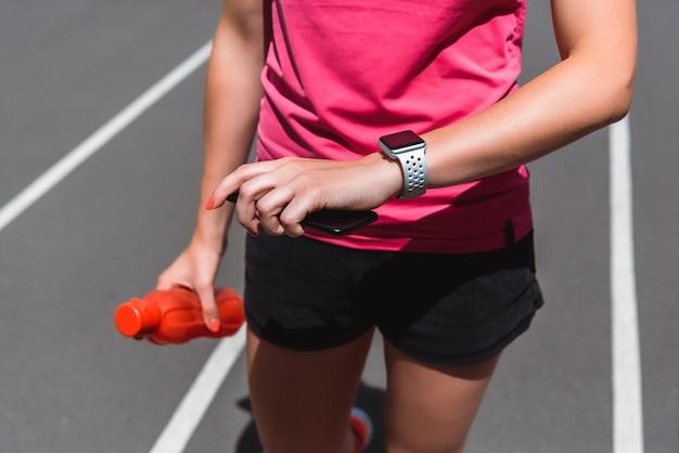 Обрезанное мнение спортсменки, глядя на smartwatch, держа бутылку спорта на беговой дорожке