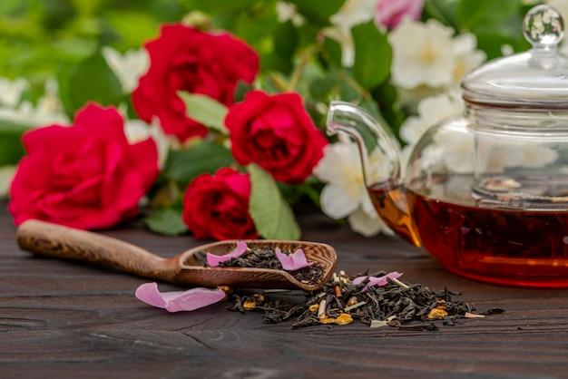 Обрезанный вид бамбуковой ложки с чаем среди цветущих кустов роз и жасмина