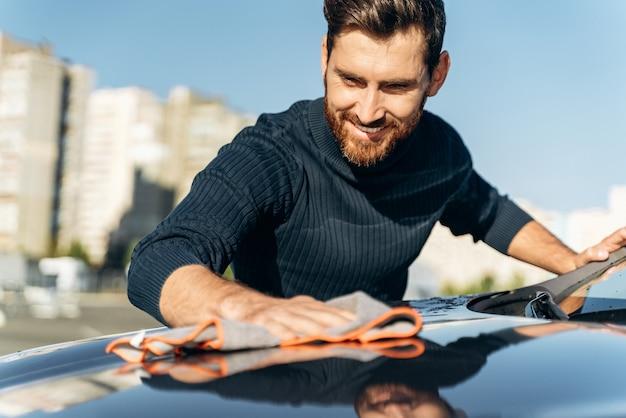 회색 극세사 닦음으로 새 전기 자동차를 닦는 수염 난 남자의 모습. 잘생긴 백인 남자가 기쁨의 미소로 차를 닦고 닦습니다. 세차 개념
