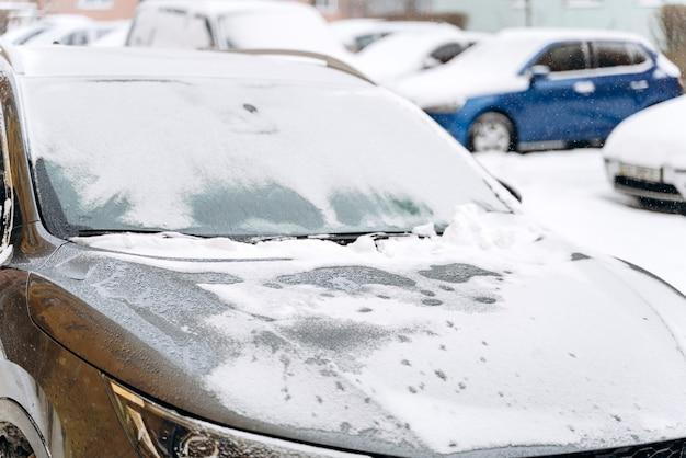 降雪後の雪の下での車のボンネットのトリミングされたビュー。雪に覆われた駐車場の車。雪の降る冬とたくさんの雪のコンセプト