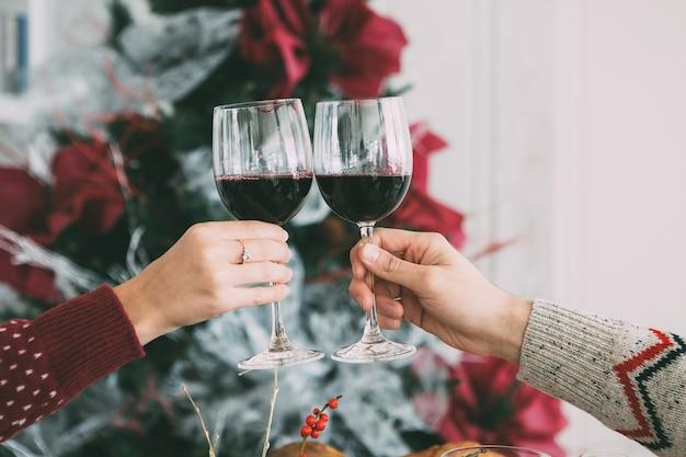 ワイングラスで乾杯する女性と男性の手のトリミングされたビュー