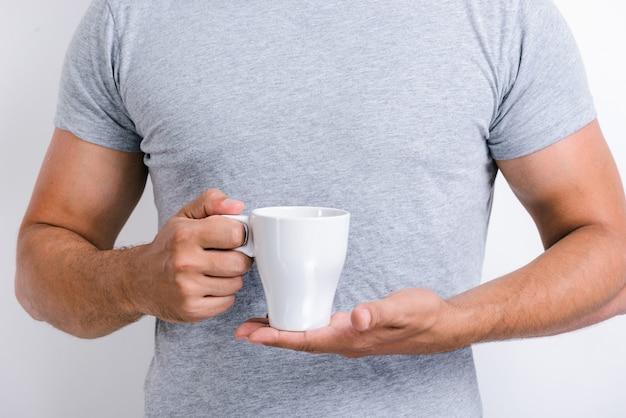 카메라 앞에서 포즈를 취하면서 아침 차나 커피 한 잔을 들고 서 있는 잘생긴 남자의 모습. 스톡 사진
