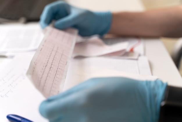 클리닉의 테이블에 앉아 있는 동안 심전도를 들고 진단을 보는 남성 의사의 자른 보기. 심장내과 과장. 의학 개념