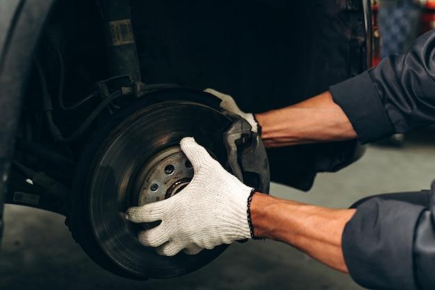 人間の車検測定量膨らんだゴムタイヤ車のトリミング図。タイヤと黒い車を持っているクローズアップの手。自動車のタイヤ空気圧測定。自動車産業の概念