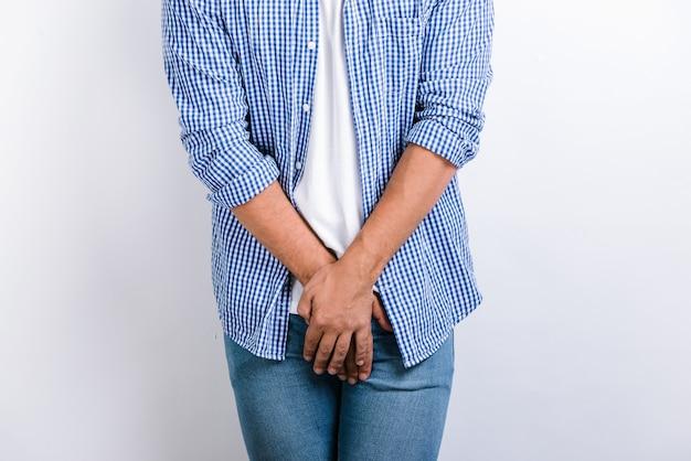 흰색 배경을 가진 스튜디오에서 포즈를 취하는 동안 성기에 손을 잡고 있는 남자의 잘린 보기. 비뇨기과 질환, 배뇨 개념 중 통증