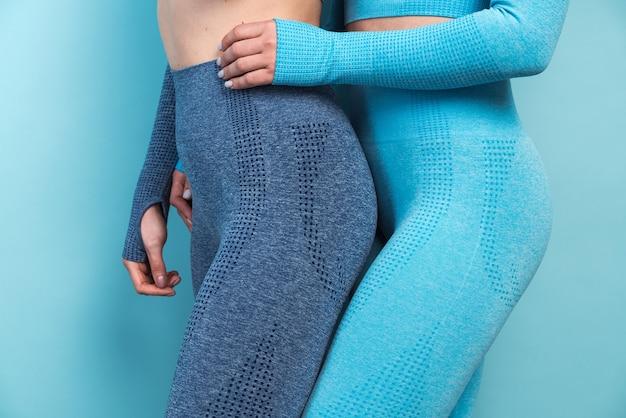 青い壁に向かってポーズをとっている間、互いに結合している異なるスポーツ服を着た2人の女性のトリミングされたビュー。スポーツとレクリエーションの概念