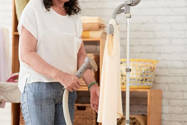 Обрезанный вид неузнаваемой женщины, пропаривающей одежду