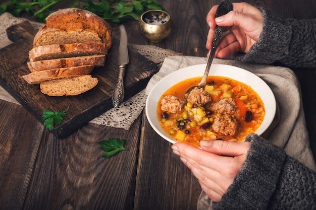소박한 나무 테이블에 미트볼과 야채 수프를 먹는 여자의 자른보기.