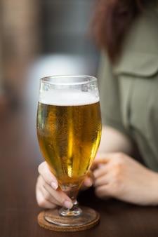 Обрезанный вид женщины, держащей стакан пива