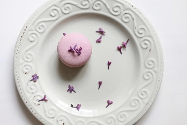 ピンクのおいしいフランスのマカロンまたは白い背景にライラックの花とマカロンとプレートを保持している女性のトリミングされたビュー。