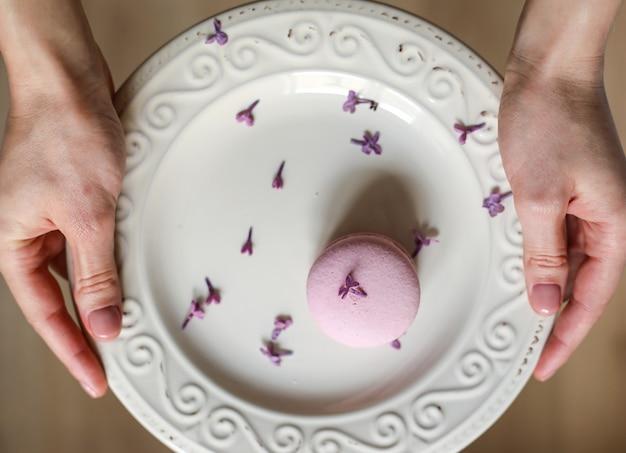 ピンクのおいしいフランスのマカロンまたは木製の背景にライラックの花とマカロンとプレートを保持している女性のトリミングされたビュー。
