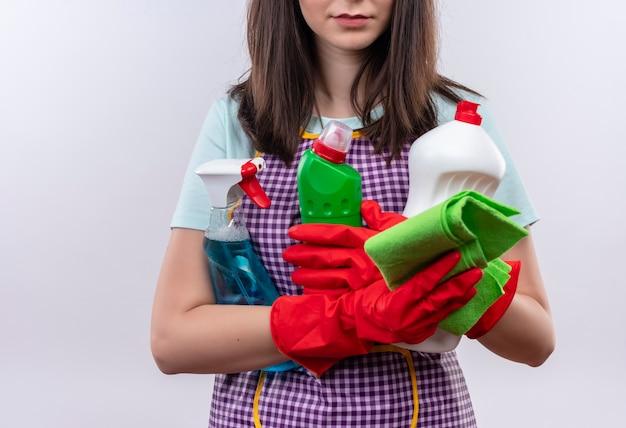 흰 벽 위에 서있는 청소 용품을 들고 앞치마와 고무 장갑에 여자의 자른보기