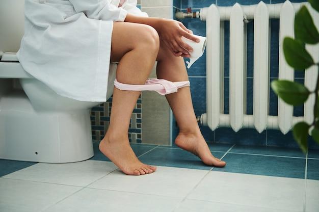 화장실에서 화장지를 손에 들고 팬티가 수축된 화장실에 앉아 있는 여성의 모습을 잘랐습니다. 근접 촬영, 의료 개념입니다.