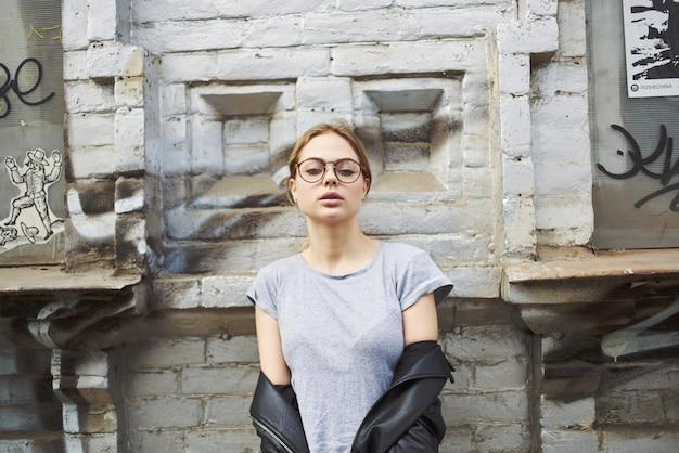 眼鏡をかけた建物の近くの革のジャケットの女性のトリミングされたビュー