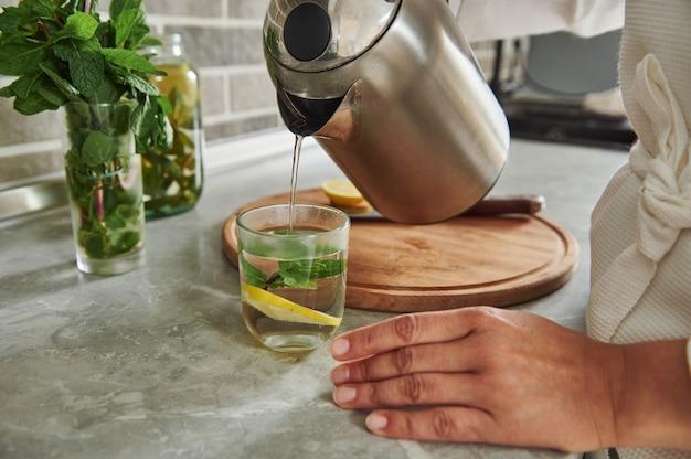 ミントの葉とレモンスライスでティーポットからグラスに水を注ぎ、ミントとレモンで健康的な水を準備しているローブの女性のトリミングされたビュー。閉じる。