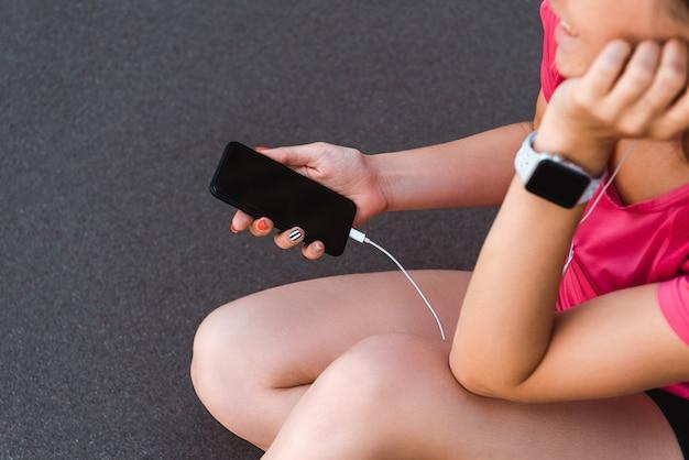 Обрезанное мнение женщины в smartwatch держит смартфон с пустым экраном на беговой дорожки