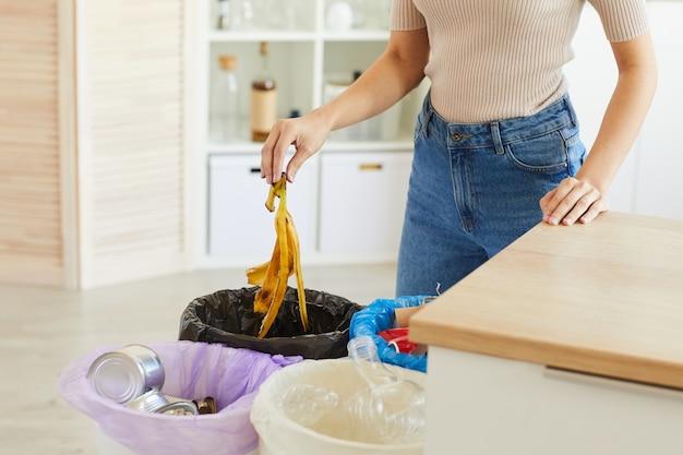 バナナの皮をゴミ箱に入れる女性のトリミングされたビュー。キッチンで廃棄物を分別するためのさまざまなビン