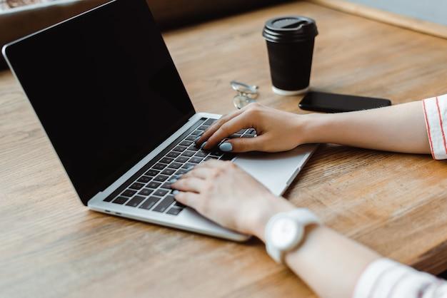 スマートフォンとコーヒーの近くの空白の画面を持つノートパソコンを使用してカフェの木製テーブルに行く女性のトリミングビュー