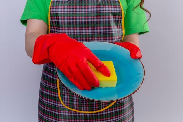 皿を洗う手で食器を保持しているエプロンとゴム手袋を着用している女性のトリミングビュー