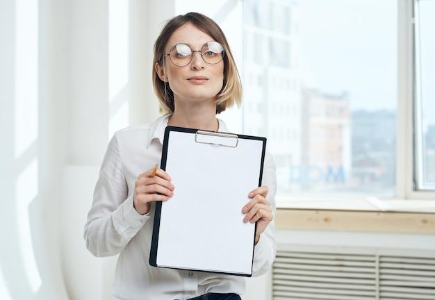Обрезанный вид женщины с папкой документов возле окна в помещении