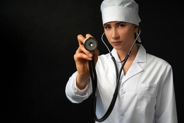 Обрезанное мнение молодая женщина-врач, удерживая стетоскоп на ее шее, студия выстрелил над черной стеной с копией пространства