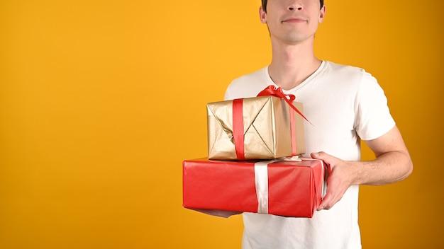 Обрезанный вид молодого красавца, держащего подарочные коробки на желтом