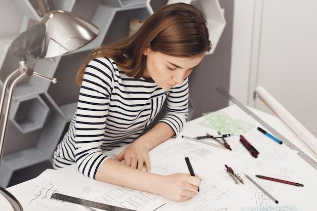 非公式の縞模様の服を着て、快適なコワーキングスペースのテーブルに座って、多くの文房具を使用して彼女の仕事をしている若いヨーロッパのフリーランスエンジニアのトリミングビュー。