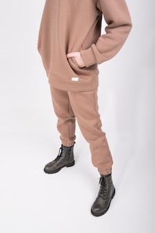 Обрезанный вид молодой женщины в серо-коричневой толстовке с капюшоном и стильных грубых сапогах, изолированных на белом. женский свитшот бежевого цвета и брюки с пустым лейблом.