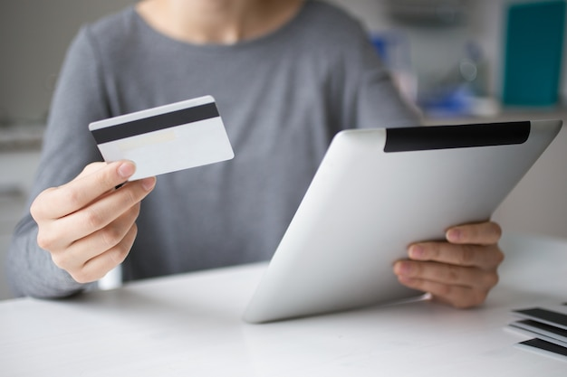 Ritagliata della persona che fa il pagamento in linea