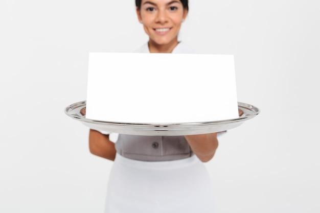 空の看板カード、トレイに選択的なフォーカスを持つ金属製のトレイを保持している若い女性ウェイターの写真をトリミング