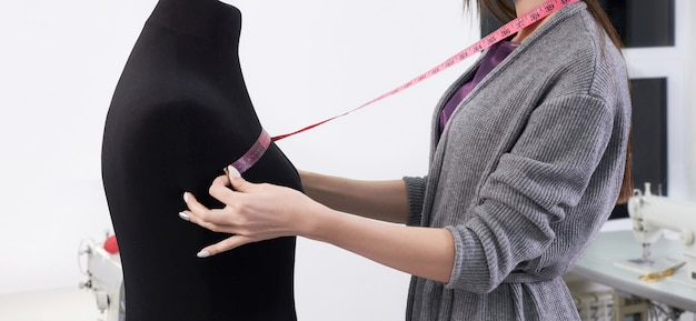 Cropped view of seamstress measuring black dummy in workshop, tailor studio work