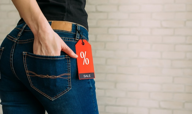 Cropped view slim woman in jeans with label black friday, copy space.