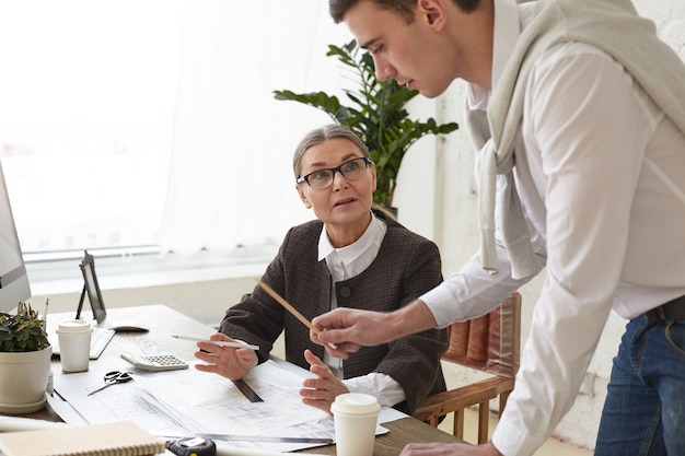 Cropped view of talented ambitious young man architect holding pencil and pointing at drawings on desk while showing construction project to his senior woman boss in glasses. working in team