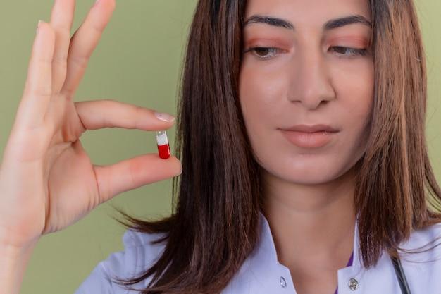 Vista potata del medico della donna che tiene la pillola in mano sul verde isolato