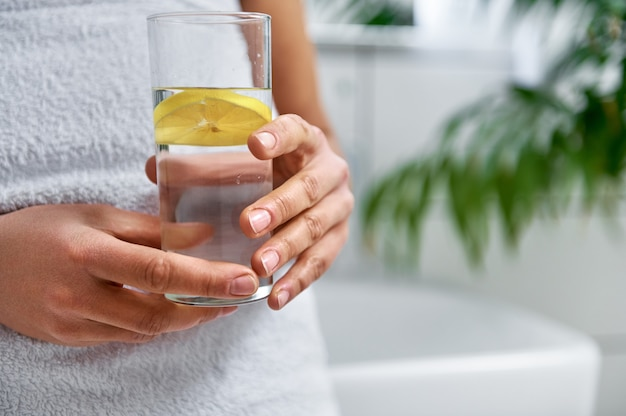 Cropped view of a woman holding a glass of water and lemon at bathroom
